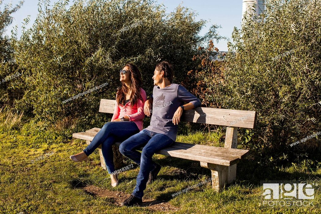 Stock Photo: Full length of young couple relaxing on park bench.