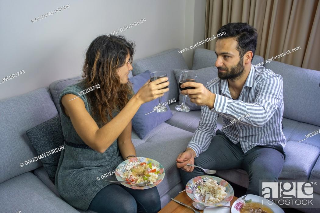 Stock Photo: happy couple making a toast and eating their handmade food in their living room interior lifestyle concept.