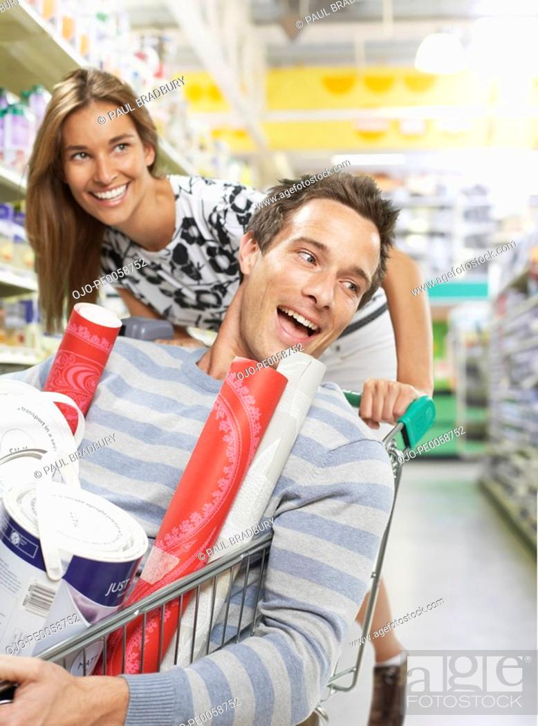 Stock Photo: Woman pushing man in shopping cart.