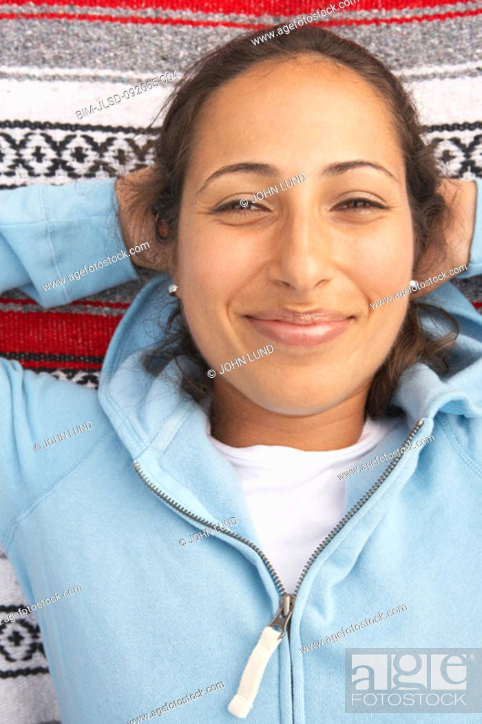 Stock Photo: Portrait of woman laying on blanket smiling.