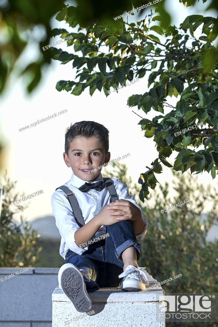 Stock Photo: Adorable little boy wearing stylish outfit posing confidently at camera sitting on fence.