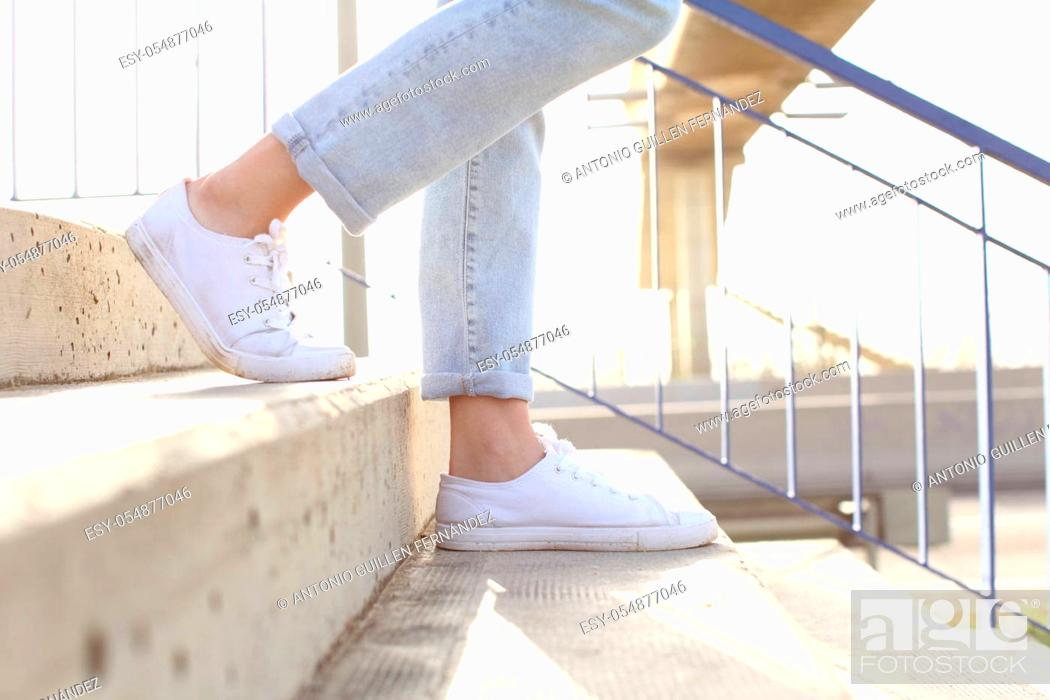 Stock Photo: Profile close up of woman legs wearing sneakers walking down stairs.