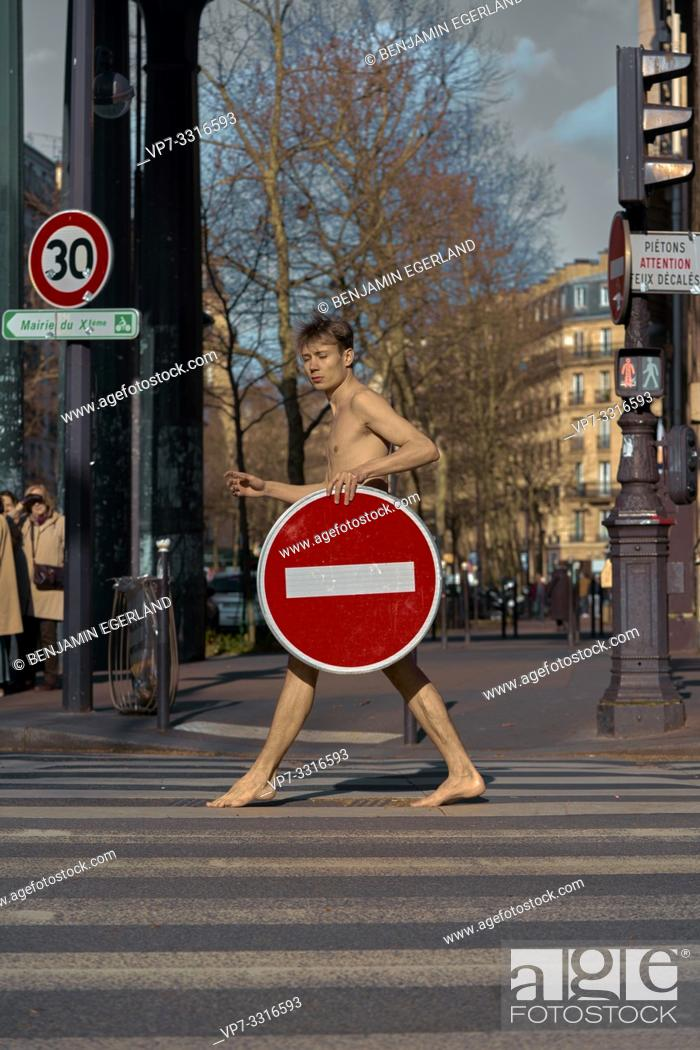 Stock Photo: young naked man with prohibition sign walking at street, in Paris, France.
