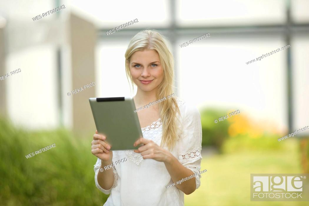 Stock Photo: Germany, North Rhine Westphalia, Cologne, Young student with digital tablet, smiling, portrait.