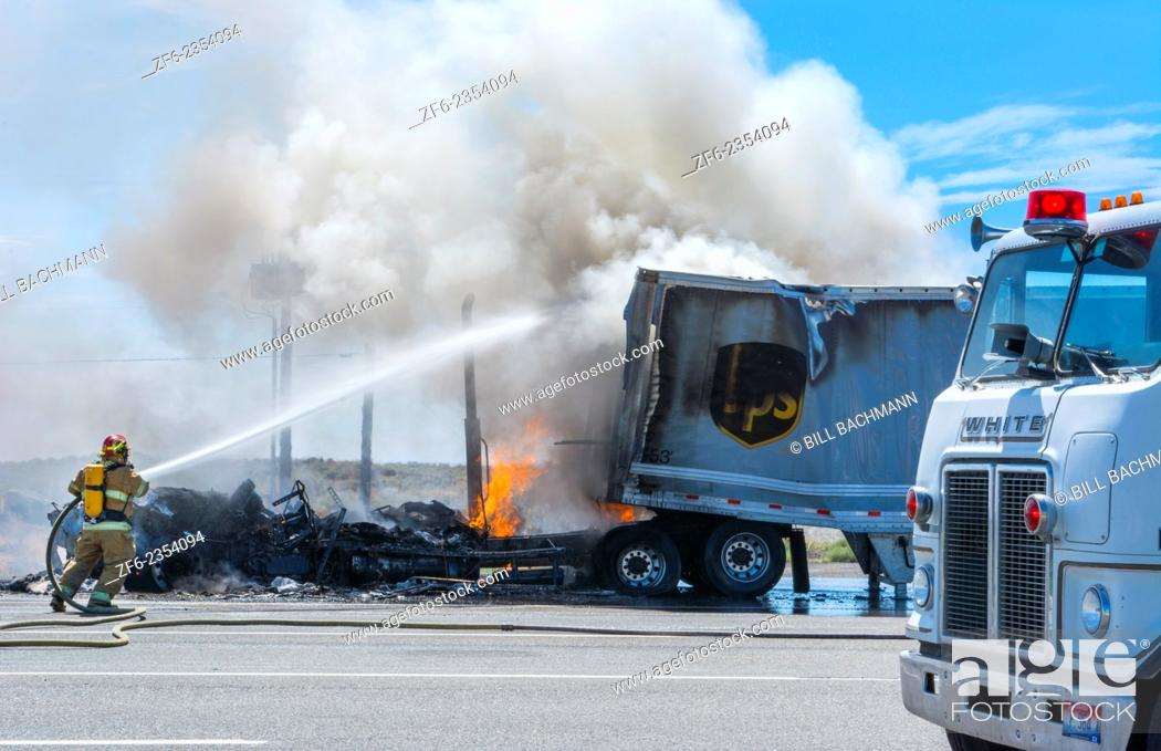 Stock Photo: Emergency fire of truck on road in Idaho near Twin Falls Idaho with firefighters and hose putting big flames and smoke out danger hot first responders.