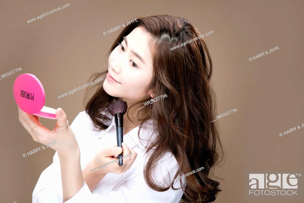 Stock Photo: Portrait of young woman using makeup brush.