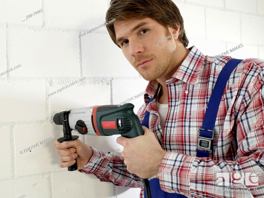 Stock Photo: Man is using a drill.