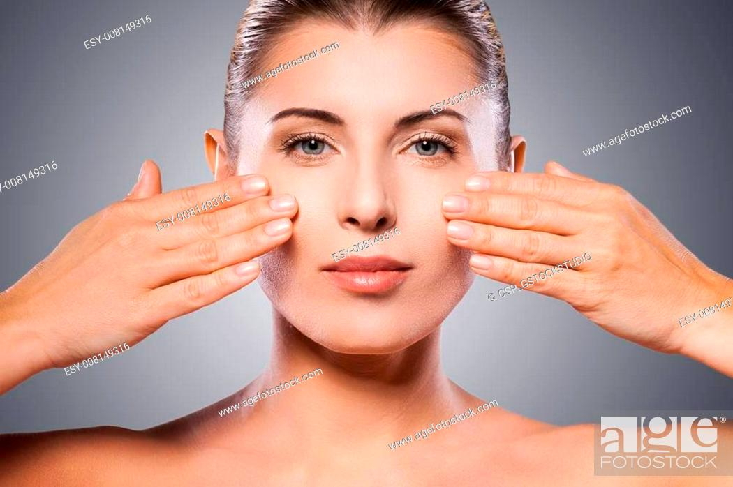 Stock Photo: Face care. Beautiful mature woman keeping eyes closed and touching face with hands while standing against grey background.