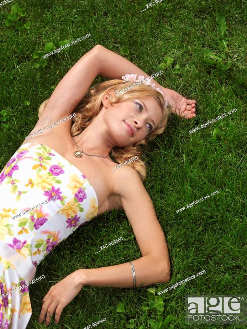 Stock Photo: Young woman in summer dress lying on green grass.