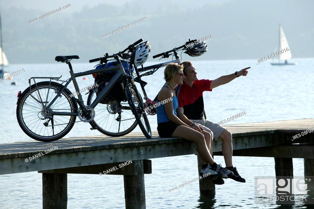 Stock Photo: Germany, Bavaria, Couple with mountain bikes taking a break on landing stage.