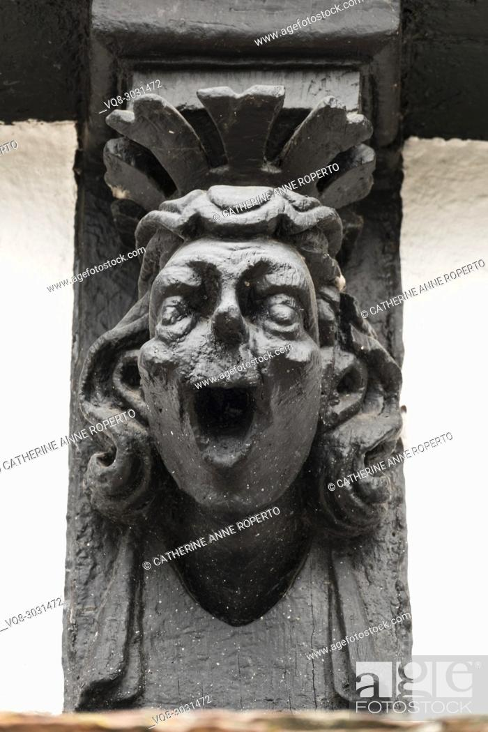 Imagen: Comic black lacquered wooden finial of a laughing man with stylised crown on the old timber framed museum of Hereford, England.