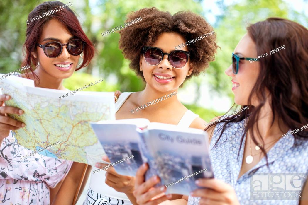 Photo de stock: women with map and city guide on street in summer.