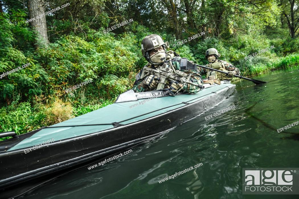 Imagen: Special forces men with painted faces in camouflage uniforms paddling army kayak. Boat moving across the river, diversionary mission, diagonal view.