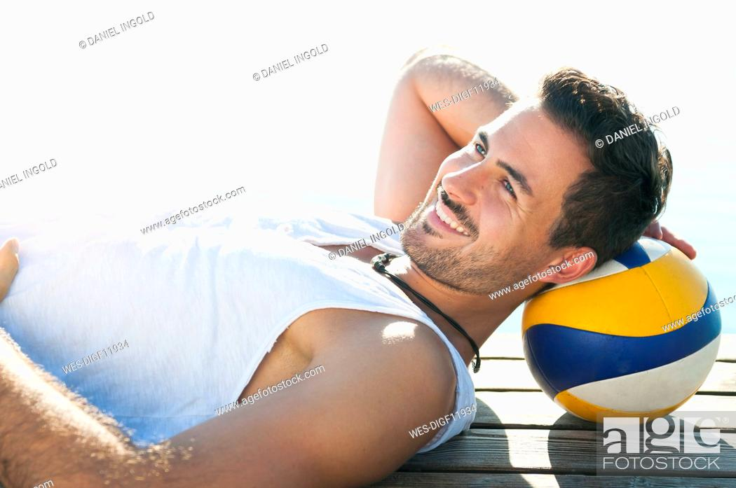 Stock Photo: Portrait of smiling young man with ball lying on jetty in front of a lake.