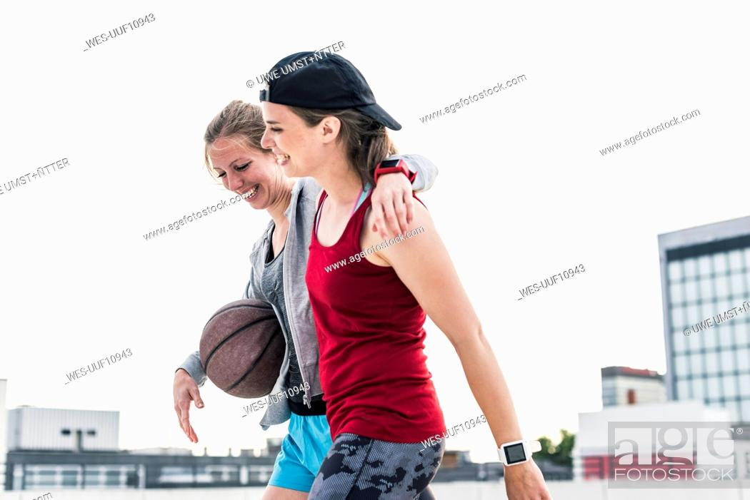 Stock Photo: Two happy women with basketball in the city.