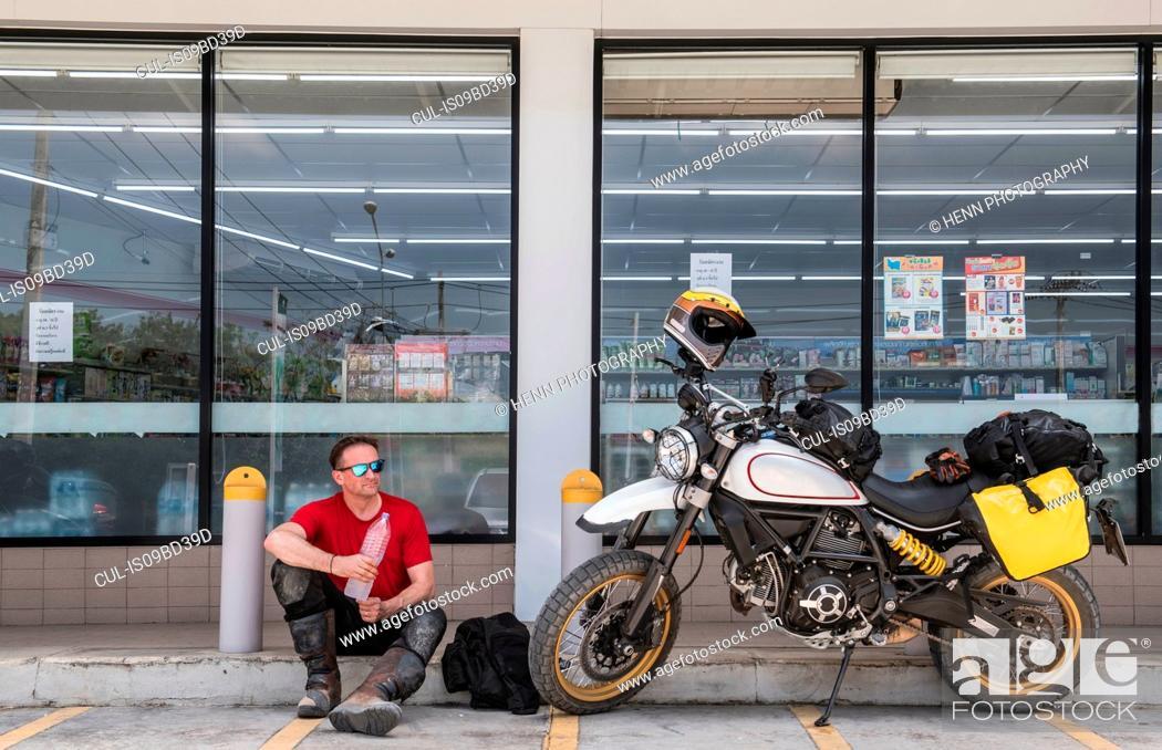 Stock Photo: Man taking break in front of shop, Pattaya, Chonburi, Thailand.