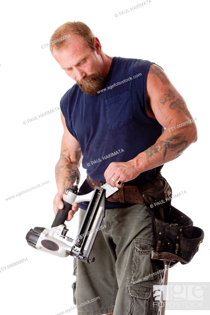 Stock Photo: Strong man with tattoos loading a nail gun with nails, wearing a tool belt with hammer, isolated.