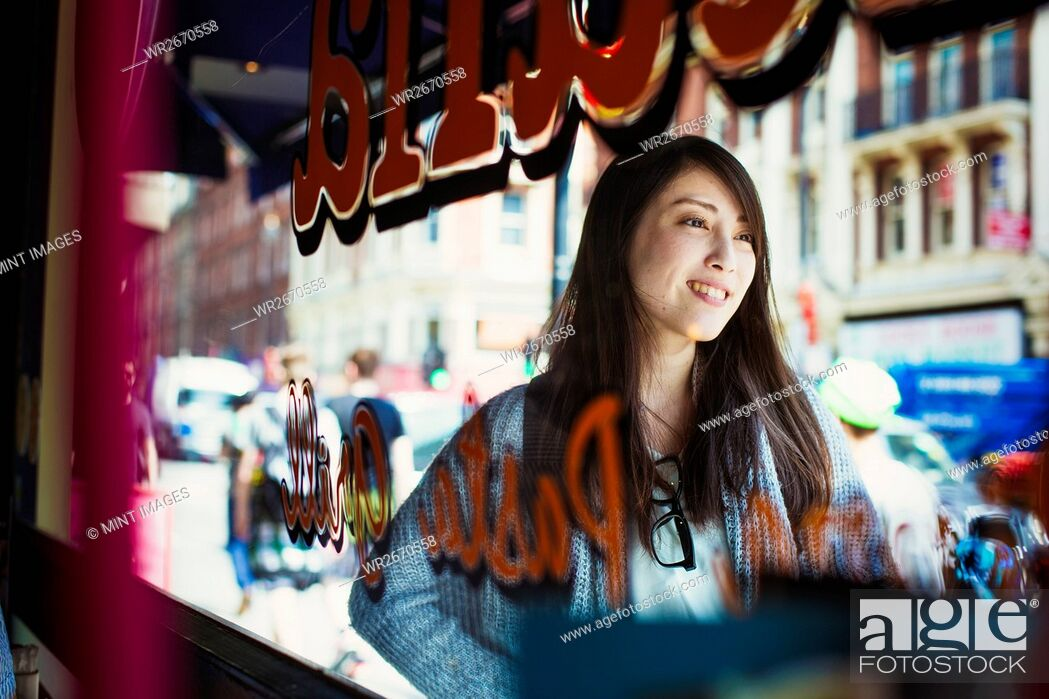 Stock Photo: Young Japanese enjoying a day out in London, walking past a shop window.