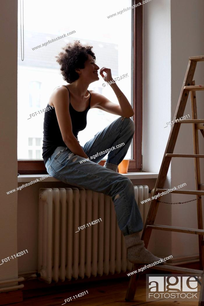 Stock Photo: A woman sitting on a window sill and resting her foot on a ladder.