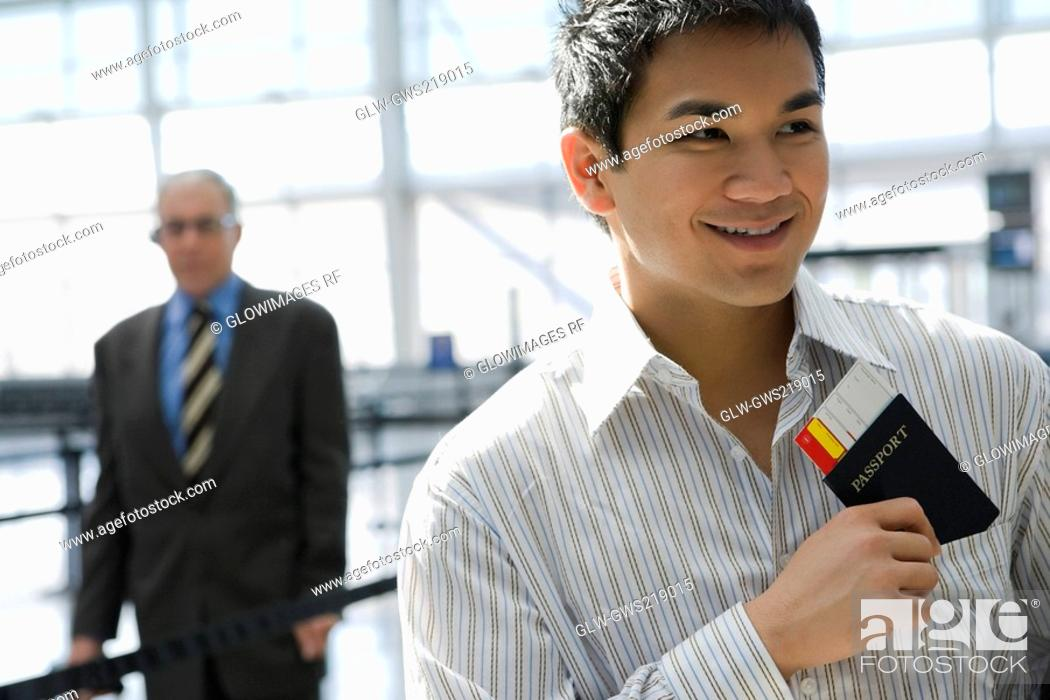 Stock Photo: Close-up of a young man putting a passport with an airplane ticket in his shirt's pocket.