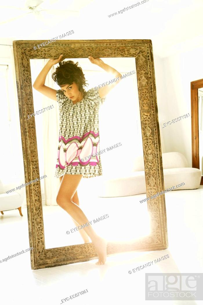 Stock Photo: Young stylish woman standing in picture frame.