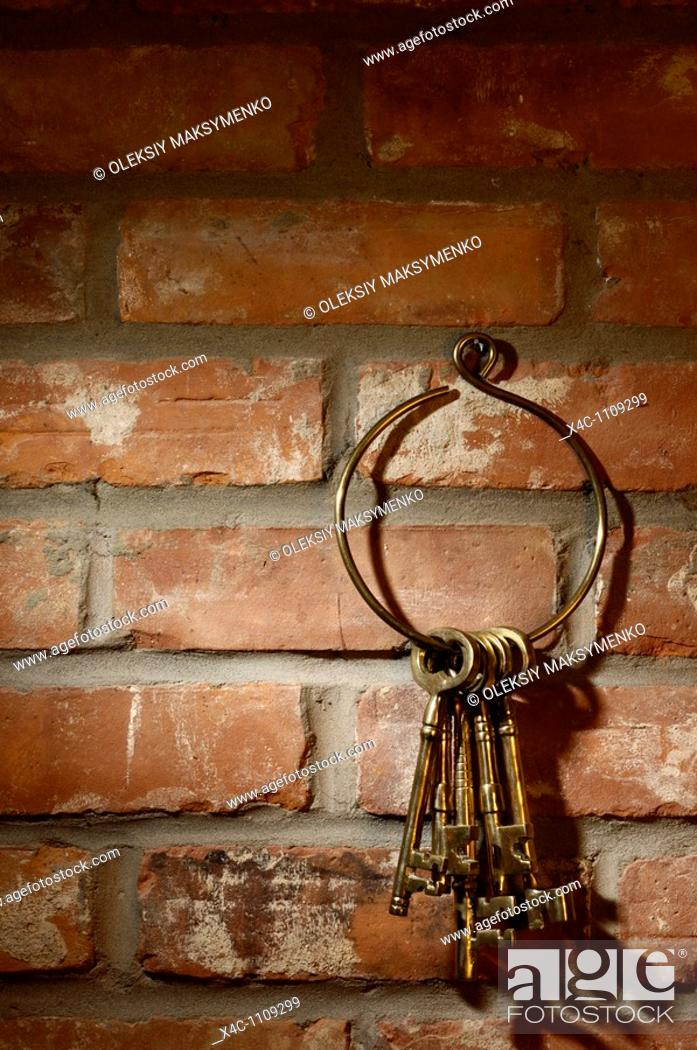 Stock Photo: Bunch of old brass skeleton keys hanging on a brick wall.