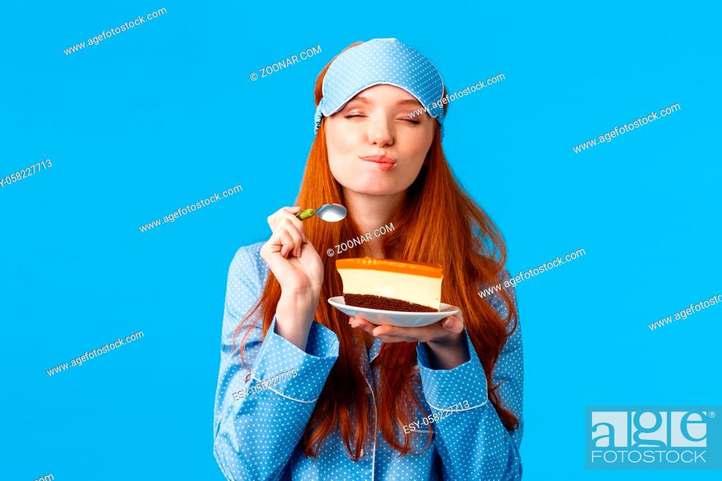 Stock Photo: Delicious food, lifestyle and people concept. Delighted and happy cute redhead female in pyjama and sleep mask, close eyes and licking lips as eating tasty cake.