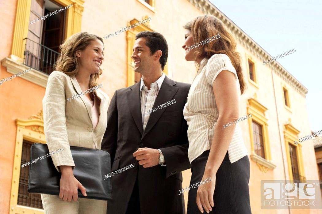 Stock Photo: Two businesswomen and one businessman standing outdoors low angle view.
