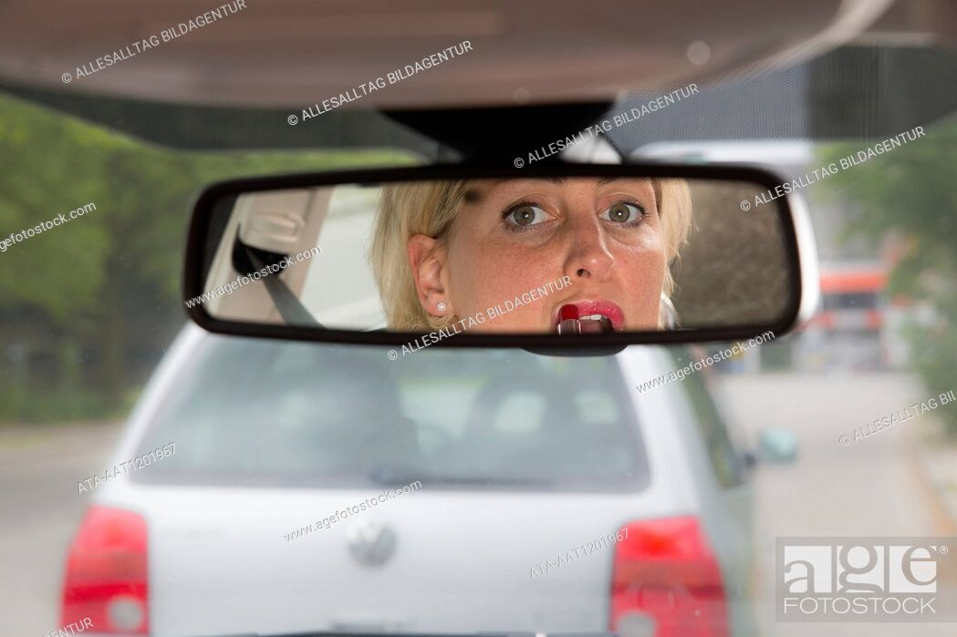 Stock Photo: Female car driver puts on lipstick.