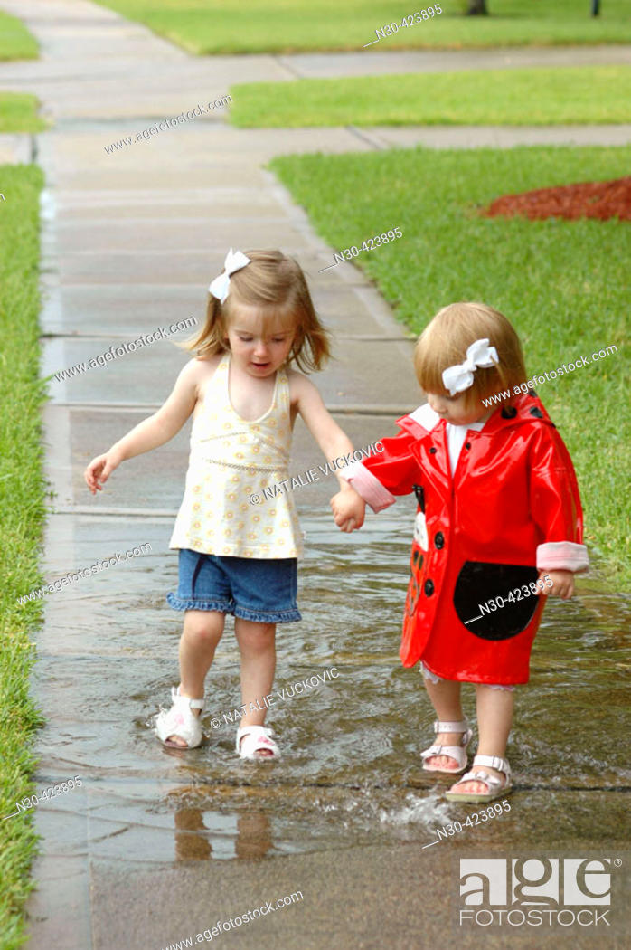 Stock Photo: Two toddlers playing in puddle.
