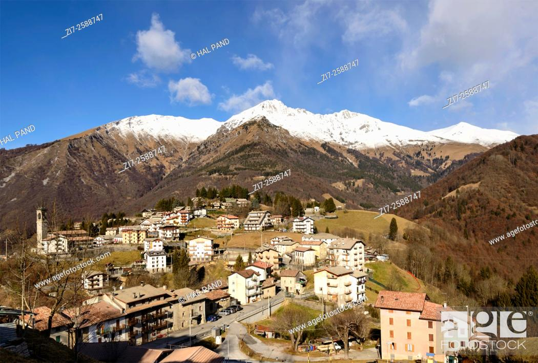 Stock Photo: landscape with mountain village among high peaks of Bergamo mountains in a winter with little snow , shot with blue sky in bright winter light.
