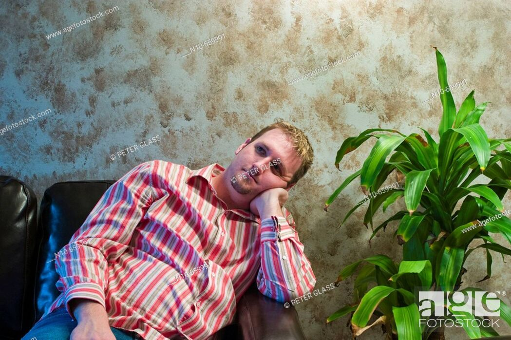 Stock Photo: Young man sitting next to a plant.