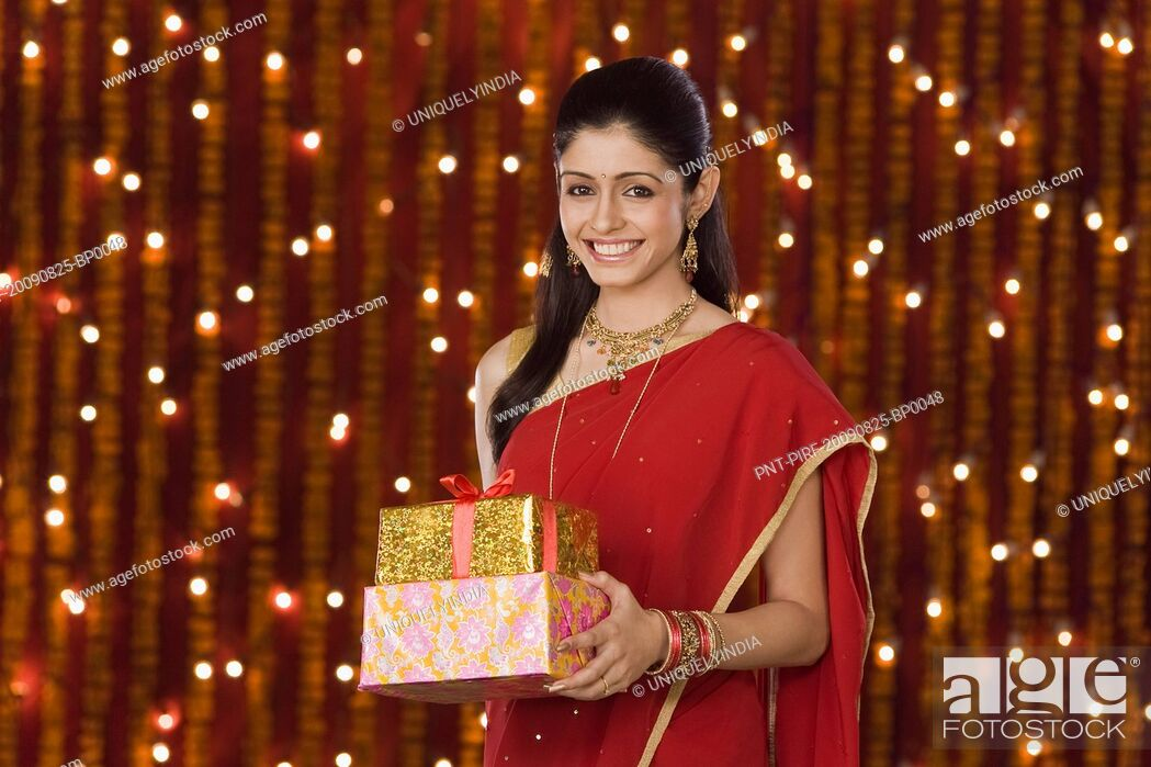Imagen: Woman holding Diwali gift and smiling.