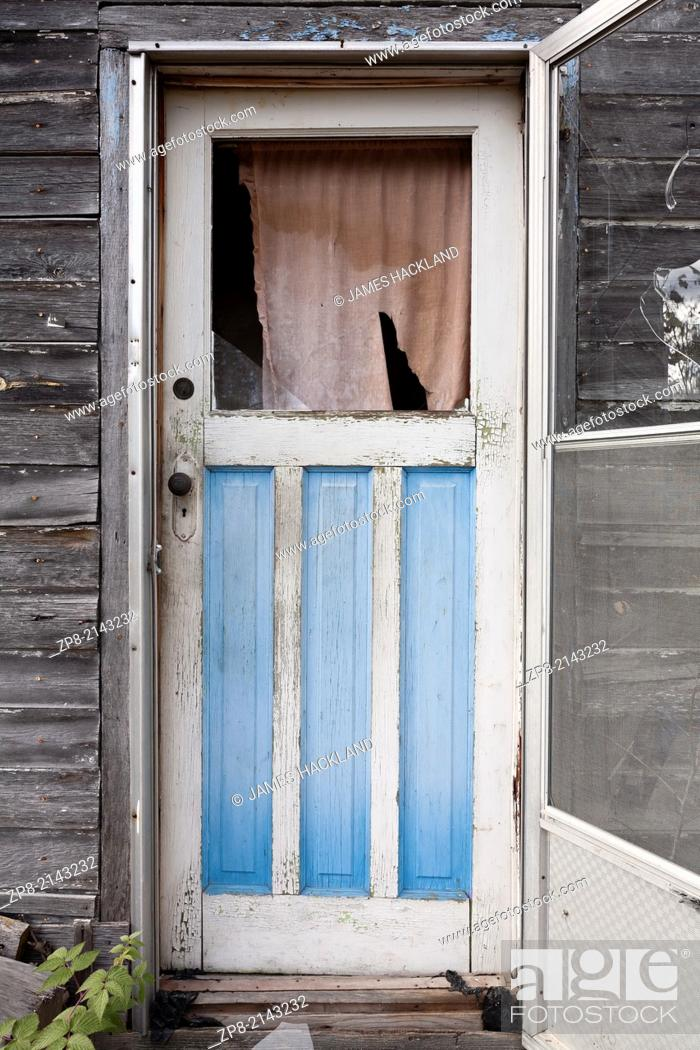 Stock Photo: An exterior weathered wooden door with a broken window pane found outside an abandoned house in the Parry Sound District of Northern Ontario, Canada.