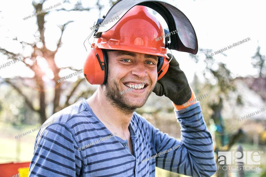 Stock Photo: Young man wearing working helmet and ear defenders, portrait.
