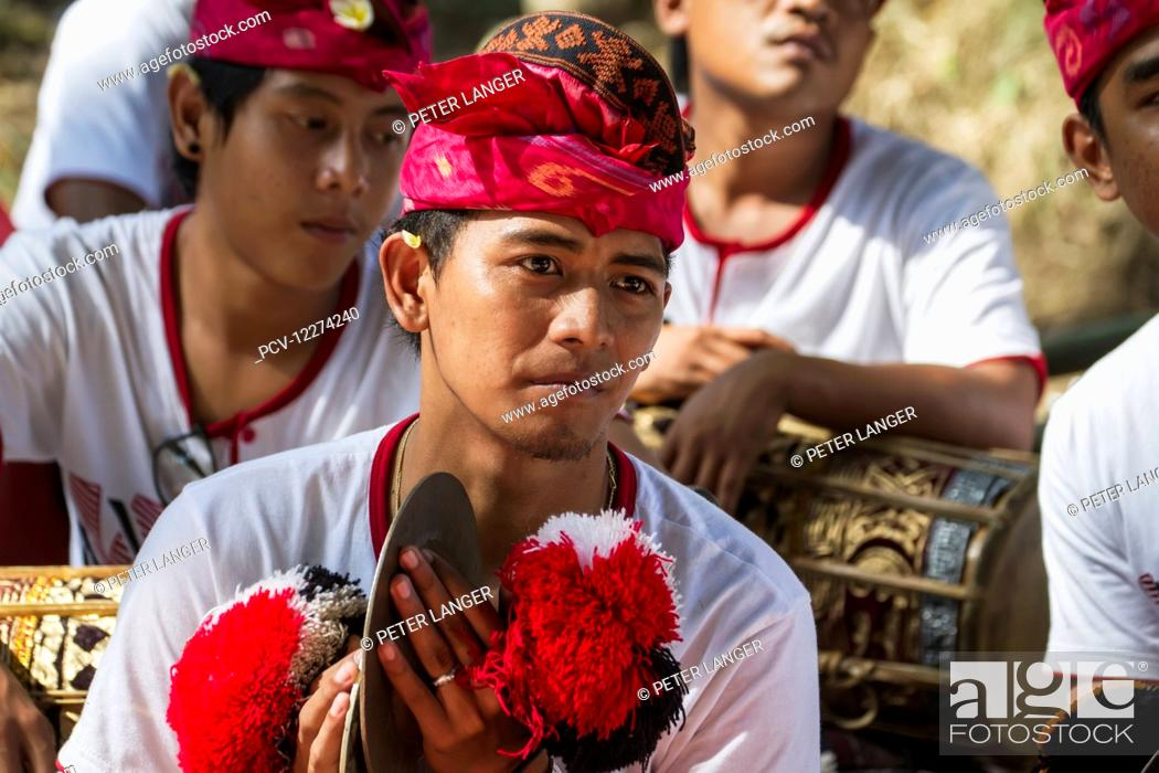 Stock Photo: Man in a gamelan ensemble preforming during a Ngaben or Cremation Ceremony, Klungkung, Bali, Indonesia.
