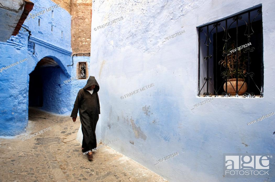 Stock Photo: Man dressed traditionally walking in a street in the Chefchaouen Old Town Medina, Morocco.
