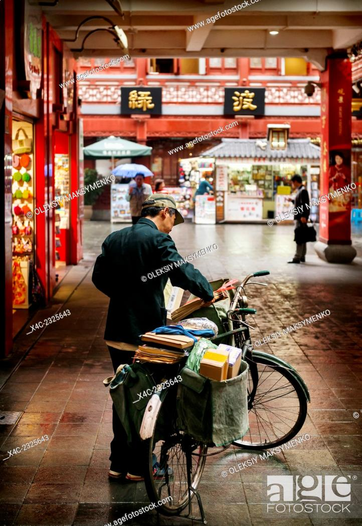 Stock Photo: Postman delivering mail by bike in the Old city of Shanghai, China 2014.