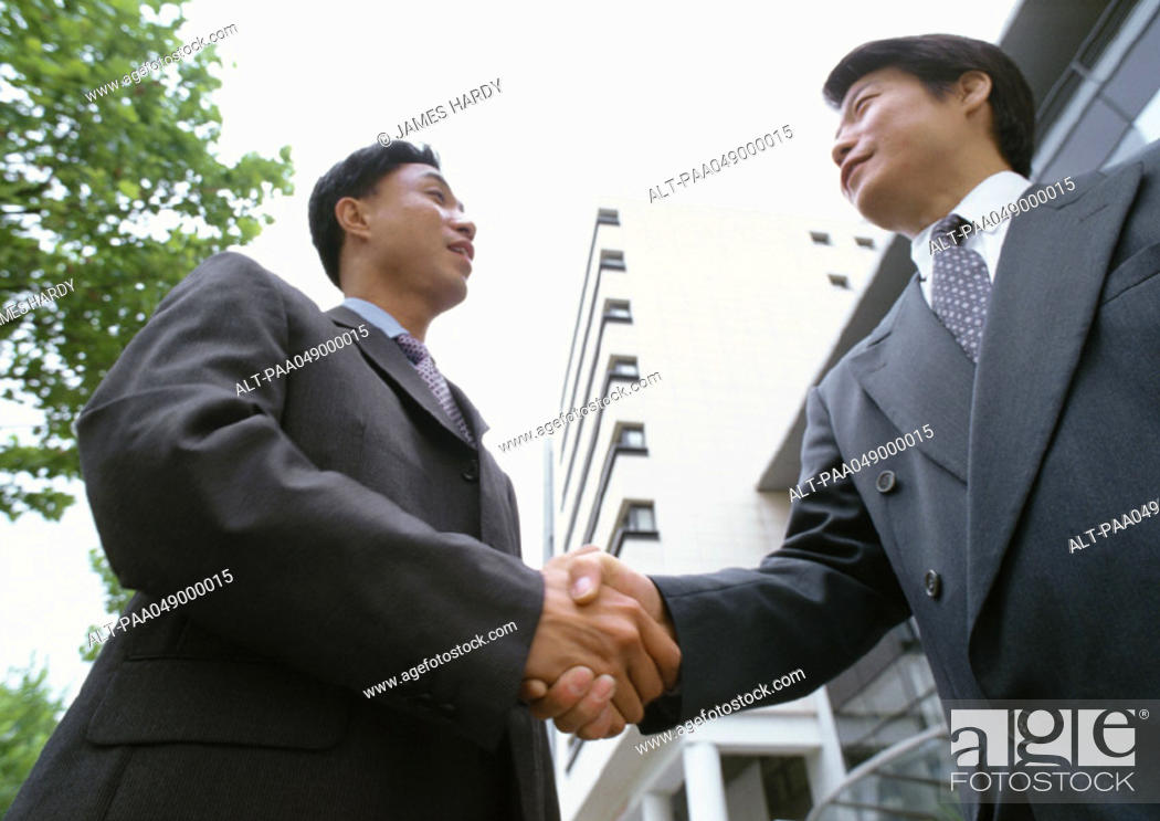 Stock Photo: Two men shaking hands, low angle view.