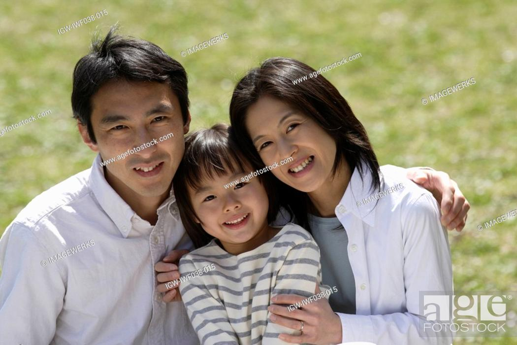 Stock Photo: Portrait of parents smiling with daughter.