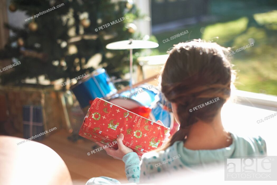 Stock Photo: Over shoulder view of girl sitting on living room floor opening christmas gift.