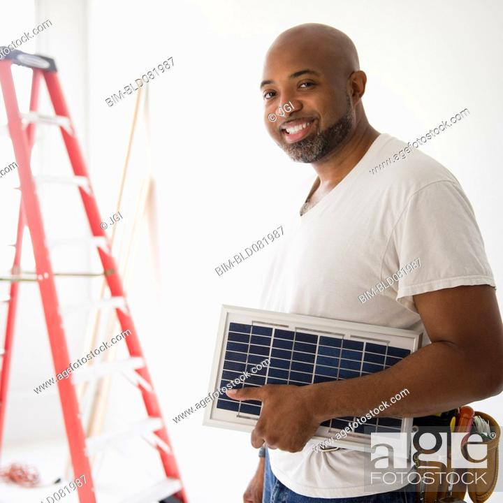 Stock Photo: African American construction worker carrying solar panel.