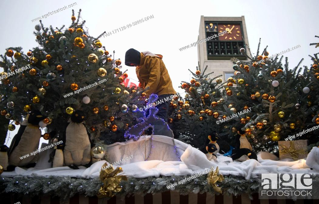 Stock Photo: A worker decorating a stall during construction of the Christmas Market in Stuttgart, Germany, 28 November 2017. Photo: Marijan Murat/dpa.