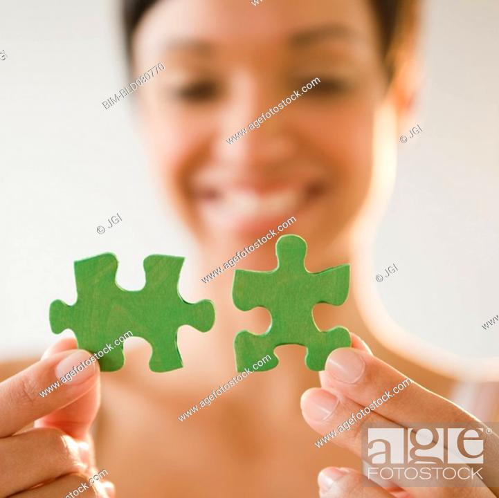 Stock Photo: Mixed race woman holding green jigsaw puzzle pieces.