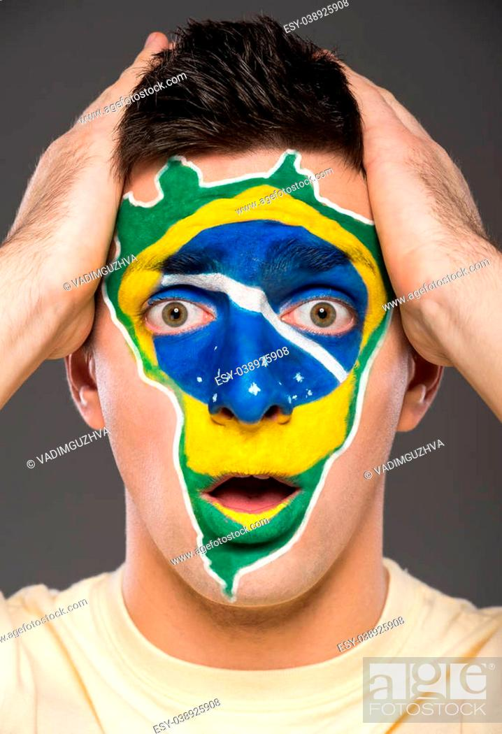 Imagen: Portrait of young man with brazilian flag painted on his face.