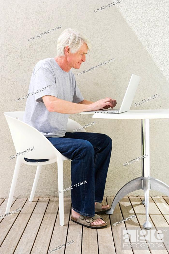 Stock Photo: Middle aged man sitting on desk and using laptop.