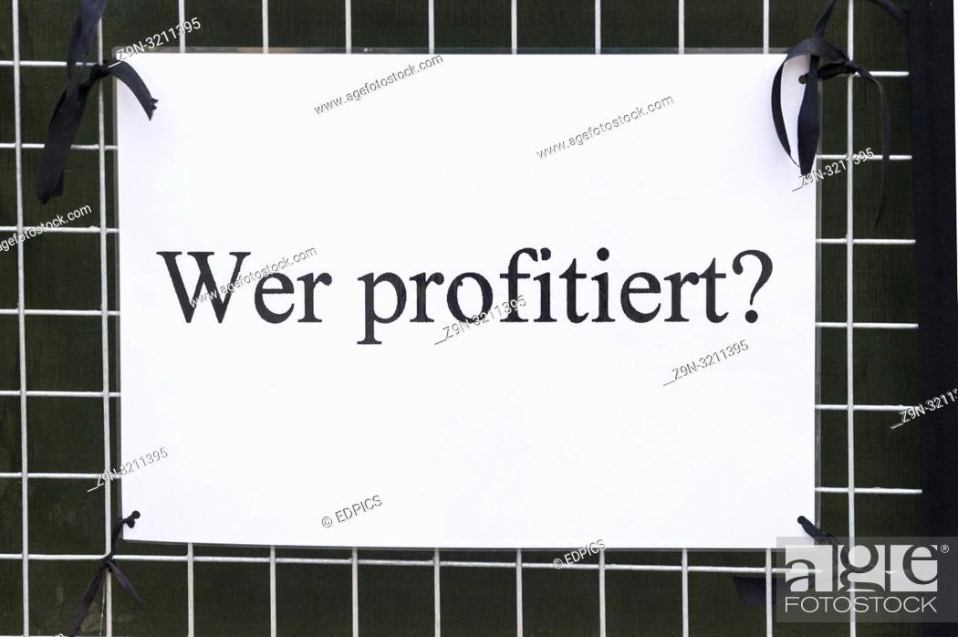 "Imagen: poster with a text that reads:""""who will benefit?"""", stuttgart, baden-wuerttemberg, germany."