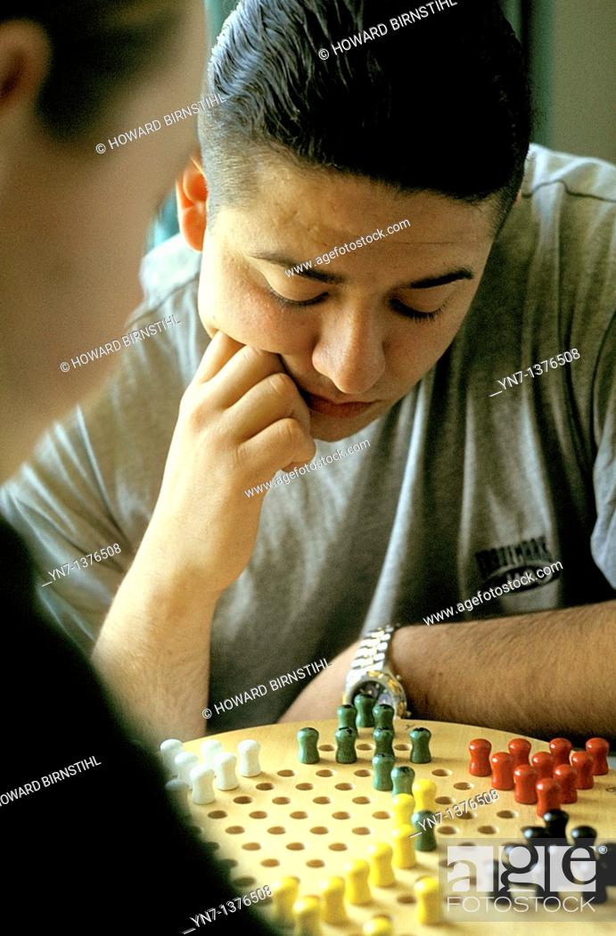 Stock Photo: close up of player as he ponders his next move on the chinese chequers board.