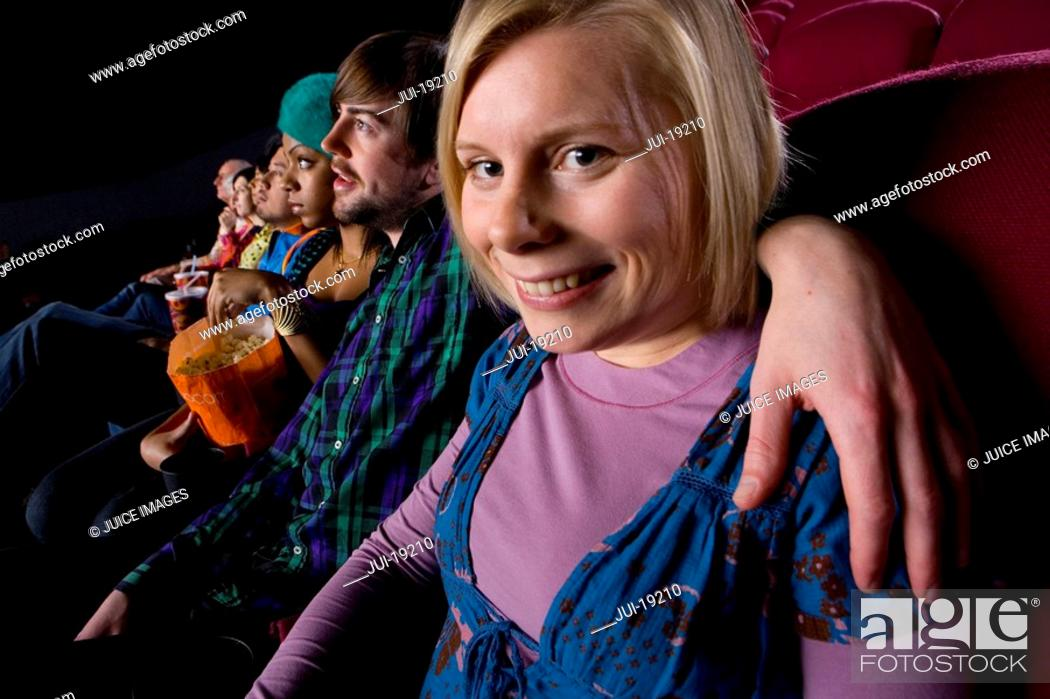 Stock Photo: Couple in cinema, portrait of woman smiling.