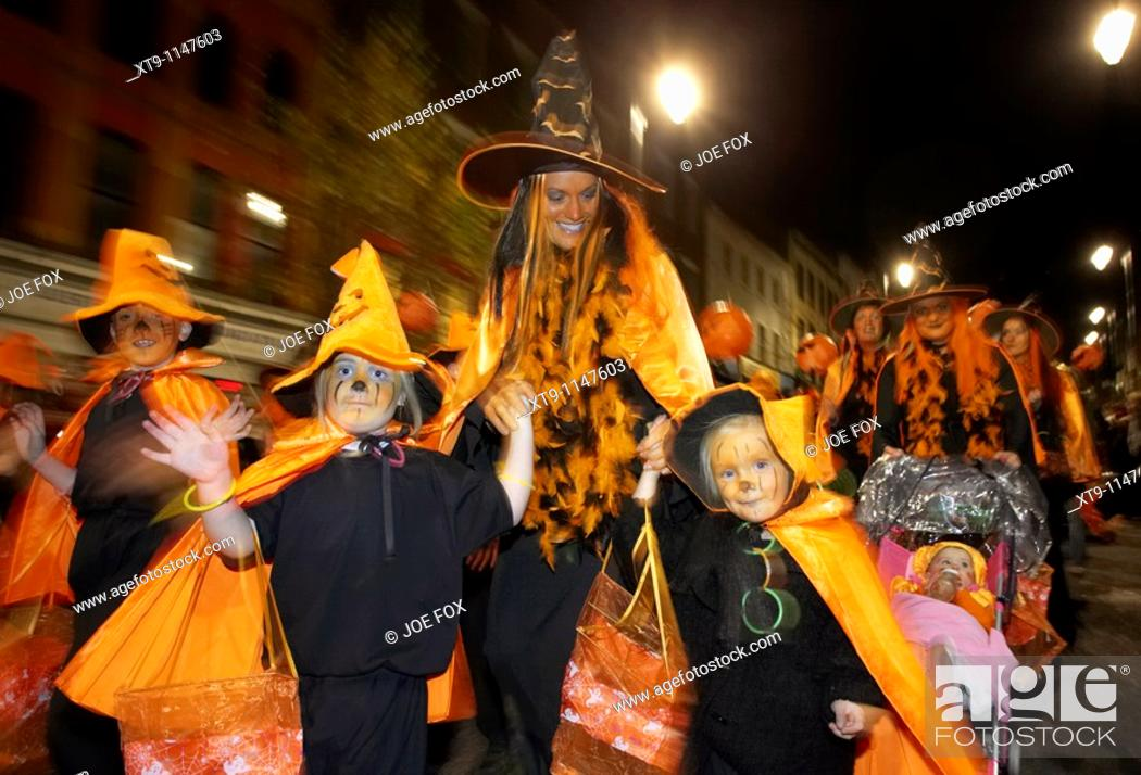 Stock Photo: schoolchildren and teachers dressed as orange pumpkins parade down shipquay street Halloween Derry Ireland.